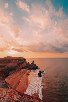 Erstaunlicher sonnenuntergang am meer, schönheit der natur. malerischer blick auf das meer, die felsige küste und den sandstrand, den goldenen himmel und die sonne. kopieren sie platz am fantastischen himmel. vertikal schießen.