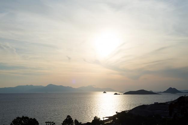 Erstaunlicher strandsonnenuntergang mit endlosem horizont und unglaublichen schäumenden wellen. vulkanische hügel im hintergrund.