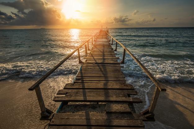 Erstaunlicher tropischer sandstrand mit hölzerner silhouettebrücke aus dem tropischen strand - promenade oder hölzerner gehweg zum horizont auf seeparadiesparadieslandschaft, sonnenaufgang oder sonnenuntergang meer dramatischer himmel