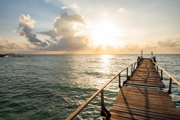 Erstaunlicher tropischer sandstrand mit silhouette-holzbrücke aus dem strand