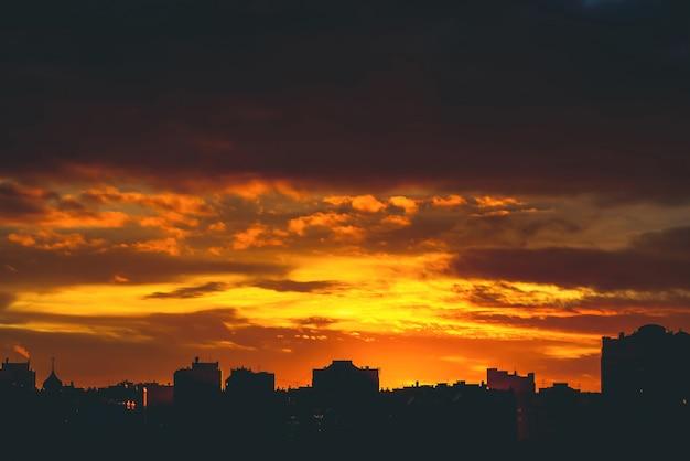 Erstaunlicher warmer drastischer bewölkter himmel über dunklen schattenbildern von stadtgebäuden.