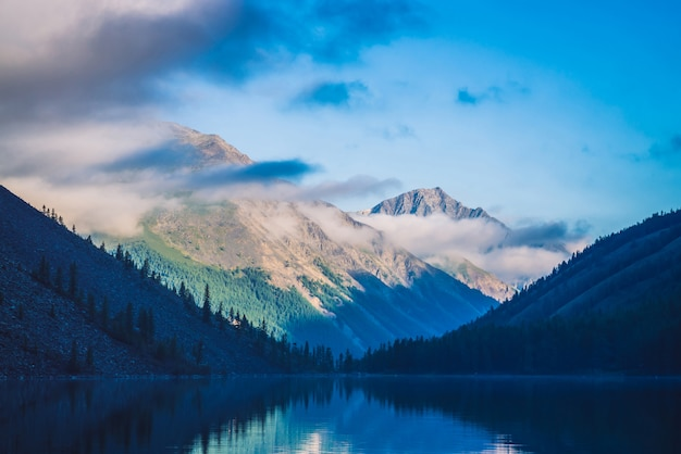 Erstaunliches blau silhouettiert berge unter blauem bewölktem himmel. schöne wellen auf wasser von gebirgssee. niedrige wolken vor gebirgskamm. wunderbare hochlandlandschaft. malerische bergwelt.