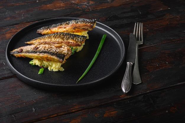 Erstaunliches gericht aus marinierter makrele mit knoblauchpaprika und safran mit weich pürierten kartoffeln auf dunklem holztisch