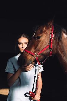 Erstaunliches junges mädchen, das draußen sitzt und ihr pferd umarmt