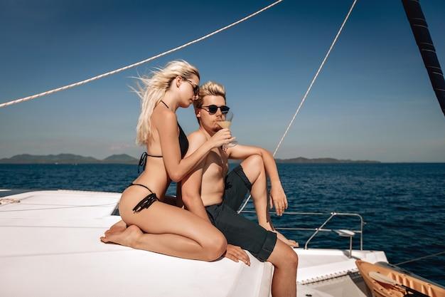 Erstaunliches junges paar, das auf ihrer riesigen laxury-yacht aufwirft. charmantes mädchen, das ein kaltes getränk in der hand hält und ihrem freund einen vorgeschmack darauf gibt.