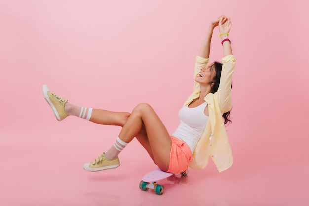 Erstaunliches lateinamerikanisches mädchen in den rosa gestreiften socken, die das leben genießen und lächeln. anmutige junge frau mit dunklem haar posiert mit den händen nach oben und sitzt auf skateboard