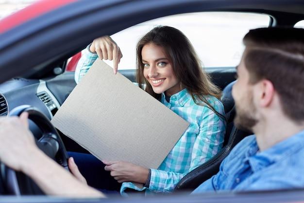 Erstaunliches mädchen, das eine tablette hält, junges paar, das im auto sitzt und kamera betrachtet, lächelnd, glücklich, kopierraum, modell, zeigt auf tablette.