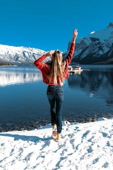 Erstaunliches mädchen, das spaß draußen im freien hat, genießt die perfekte naturansicht. blauer klarer himmel, große berge und see. winter kaltes wetter. warmer roter strickpullover und röhrenjeans.