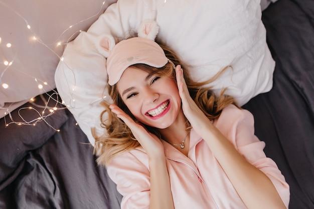 Erstaunliches mädchen im rosa nachtanzug, der auf kissen liegt und lacht. überkopfporträt der reizenden blonden frau, die morgen im bett genießt.
