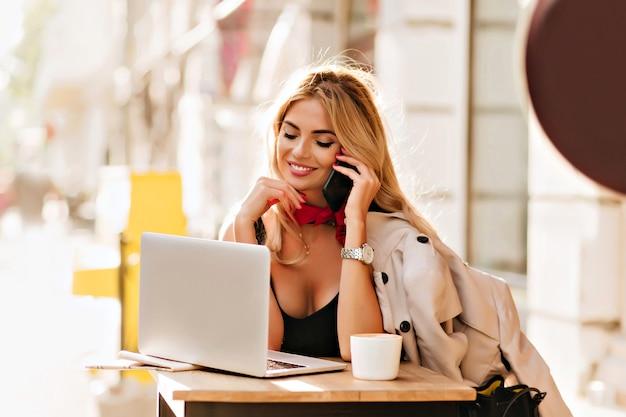 Erstaunliches mädchen in guter laune, das am telefon spricht und auf computerbildschirm schaut