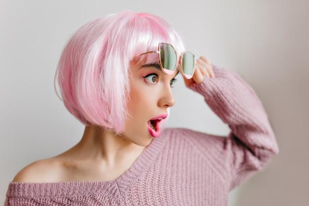 Erstaunliches mädchen in rosa peruke, das mit erstaunen aufwirft und wegschaut. charmantes weibliches modell in der bunten perücke, die auf lichtwand in gläsern steht.