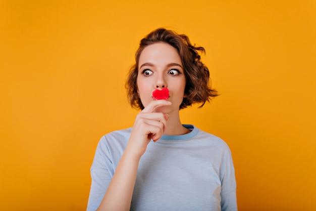 Erstaunliches mädchen mit großen braunen augen, die mit kleinem rotem herzen aufwerfen. wunderbares weibliches modell mit trendiger gewellter frisur, die auf valentinstag wartet.