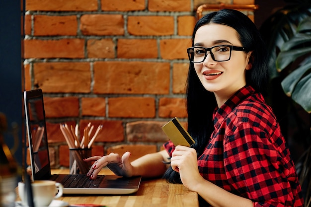 Erstaunliches mädchen mit schwarzen haaren, die brillen tragen, die im café mit laptop, handy, kreditkarte und tasse kaffee sitzen, freiberufliches konzept, online-shopping, rotes hemd tragend.