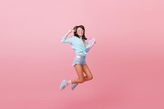 Erstaunliches modisches lateinamerikanisches mädchen im straßenoutfit, das mit skateboard springt. trendy frau in jeansshorts und gestreiften socken, die spaß haben