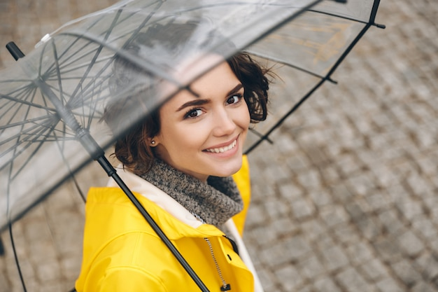 Erstaunliches porträt der jungen frau im gelben mantel, der unter transparentem regenschirm mit breitem aufrichtigem lächeln steht