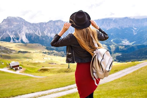 Erstaunliches reiseerlebnisbild der schönen stilvollen frau, die zurück aufwirft und den atemberaubenden blick auf die berge betrachtet