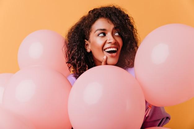 Erstaunliches schwarzes weibliches modell mit partyballons, die auf orange aufwerfen. entzückende brünette frau, die spaß während des ereignisses hat.