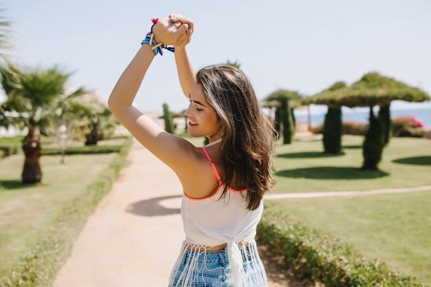 Erstaunliches süßes mädchen mit braun glänzendem haar posiert gerne mit den händen nach oben. schlanke anmutige junge frau im weißen hemd lächelnd und tanzend im park auf sommerresort im sonnigen morgen