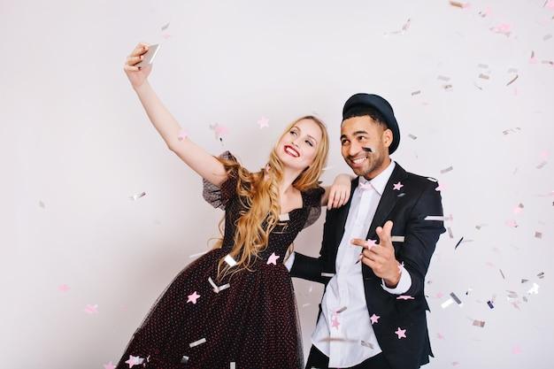 Erstaunliches süßes verliebtes paar, das große party in lametta feiert und selfie macht. luxus abendkleidung, strahlend positive emotionen