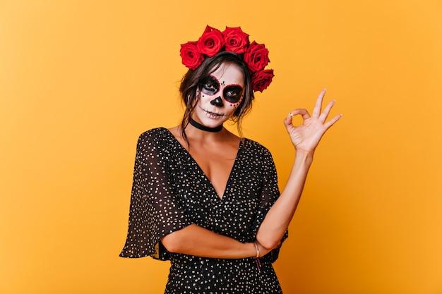 Erstaunliches totes mädchen mit unheimlichem make-up, das auf orange hintergrund aufwirft. studiofoto der reizenden lateinamerikanischen frau in der halloween-kleidung.