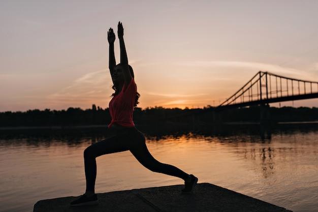 Erstaunliches wohlgeformtes mädchen, das yoga auf sonnenaufgang tut. schönes weibliches modell, das sonnenuntergangsansichten während des trainings genießt.