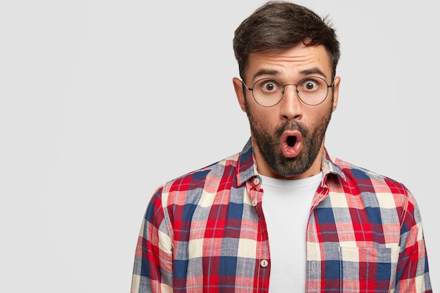 Erstaunt attraktiver unrasierter mann mit geöffnetem mund und abgehörten augen, wundert sich über die neuesten nachrichten im college