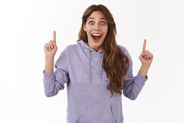 Erstaunt emotional gut aussehende junge glückliche frau lange kastanienbraune frisur nach vorne starren beeindruckt froh nach oben zeigende zeigefinger aufgeregt optimistisch teilen freund unglaublich gute promo angebot weiße wand