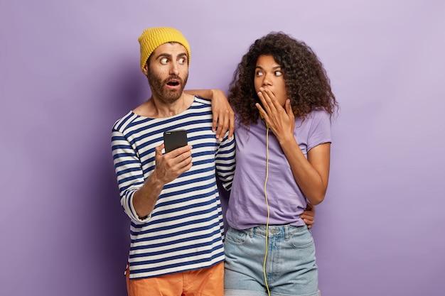 Erstaunt erschrockener freund und freundin fühlen sich überrascht von der erhaltenen e-mail auf dem smartphone, erhalten sie rabatt im lieblingswebshop