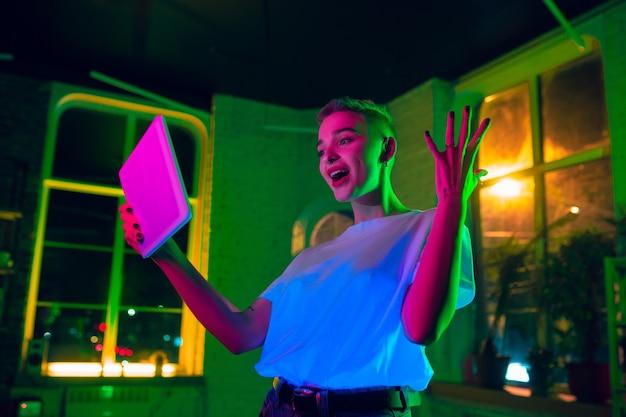 Erstaunt. filmporträt der stilvollen frau im neonbeleuchteten innenraum. getönt wie kinoeffekte, leuchtende neonfarben. kaukasisches modell mit tablette in bunten lichtern drinnen. jugendkultur.