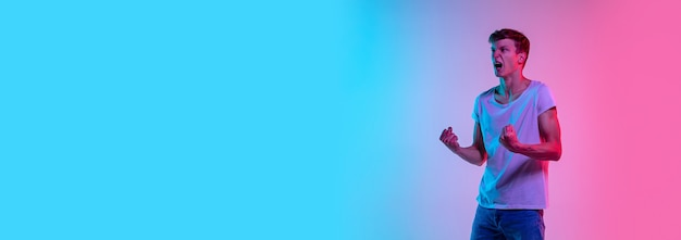Erstaunt. porträt des jungen kaukasischen mannes auf blau-rosa studiohintergrund des gradienten im neonlicht. jugendkonzept, menschliche emotionen, gesichtsausdruck, verkauf, werbung. schönes modell in lässig. flyer