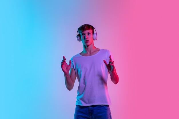 Erstaunt. porträt des jungen kaukasischen mannes auf blau-rosa studiohintergrund des gradienten im neonlicht. jugendkonzept, menschliche emotionen, gesichtsausdruck, verkauf, werbung. schönes modell in lässig.