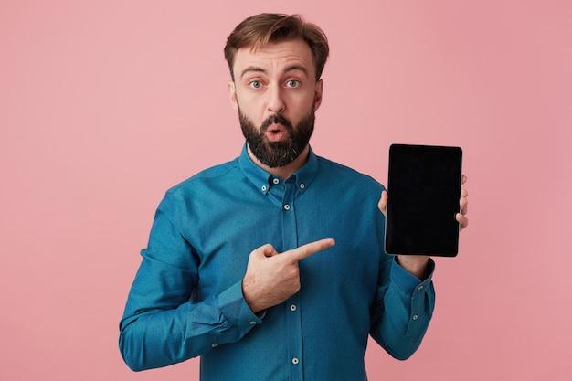 Erstaunt schockierter bärtiger mann möchte ihre aufmerksamkeit auf sich ziehen und mit dem finger auf sein gerät zeigen. betrachten der kamera in der überraschung lokalisiert über rosa hintergrund.