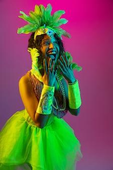 Erstaunt. schöne junge frau im karneval, stilvolles maskeradekostüm mit federn, die auf steigungshintergrund in neon tanzen. konzept der feiertagsfeier, festliche zeit, tanz, party, spaß haben.