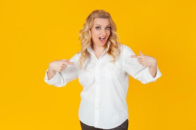Erstaunt sprachlos beeindruckt glückliche europäische blonde frau in weißem hemd zeigt auf sich selbst schockiert, mit offenem mund, herabhängendem kiefer, erstaunt.