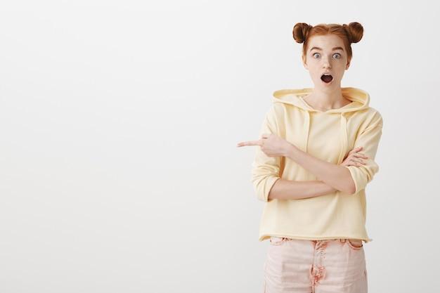 Erstaunt und beeindruckt rothaariges teenager-mädchen zeigt mit dem finger nach links