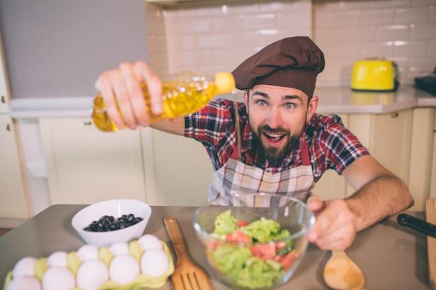 Erstaunt und glücklich kerl steht am tisch in der küche und hält eine flasche öl. er gießt etwas davon in eine schüssel mit salat. guy hält den mund offen.