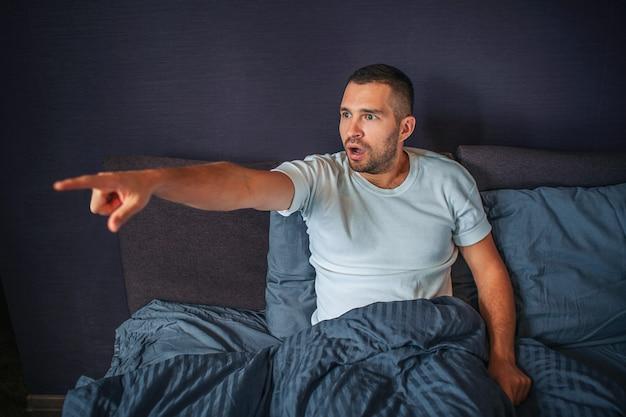 Erstaunt und verwundert sitzt ein junger mann im schlafzimmer auf dem bett und schaut nach links. er zeigt mit dem finger. guy ist begeistert.