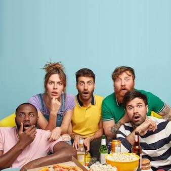 Erstaunt verbringen fünf freunde den abend zu hause, schauen nachrichtenprogrammierer, geschockt von etwas, trinken bier, essen popcorn, pizza und sandwich. emotionale menschen erwarten kein so plötzliches ende des films