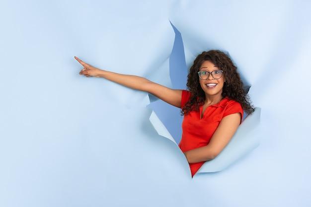 Erstaunt wunderte sich, dass sie eine fröhliche afroamerikanische frau in zerrissenem blauem papier zeigte