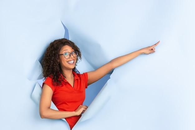 Erstaunt wunderte sich, fröhliche afroamerikanische frau in zerrissenem blauem papierhintergrund zu zeigen