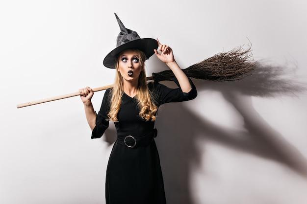 Erstaunte blonde hexe, die ihren magischen hut berührt. attraktives vampirmädchen, das sich auf karneval in halloween vorbereitet.