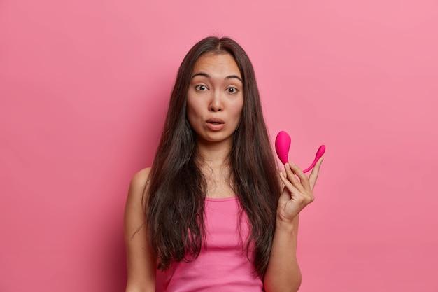 Erstaunte brünette frau hält modernen ferngesteuerten app-gesteuerten intelligenten vibrator, besucht sexshop und kauft notwendiges zubehör, um sich zu befriedigen, lässig gekleidet, posiert gegen rosa wand