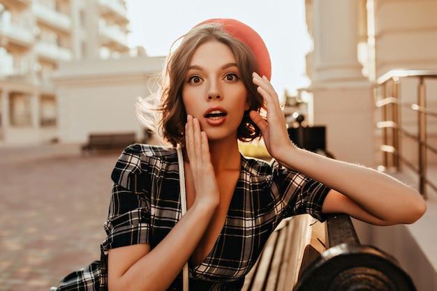 Erstaunte dame mit kurzen haaren, die an warmen tagen auf bank sitzen. außenfoto des attraktiven lockigen überraschten mädchens in der roten baskenmütze.