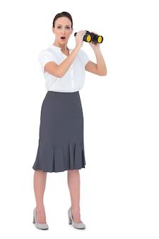 Erstaunte elegante geschäftsfrau, die ferngläser hält