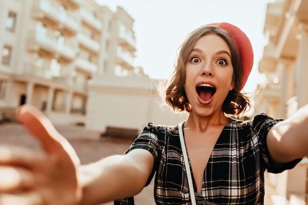 Erstaunte französische dame mit braunen augen, die selfie auf der straße machen. lustiges lockiges mädchen in der roten baskenmütze, die foto von sich selbst beim gehen durch stadt macht.