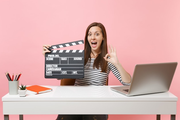 Erstaunte frau, die ein ok-schild zeigt, das klassische schwarze filmklappe hält und an einem projekt arbeitet, während sie mit laptop im büro sitzt?