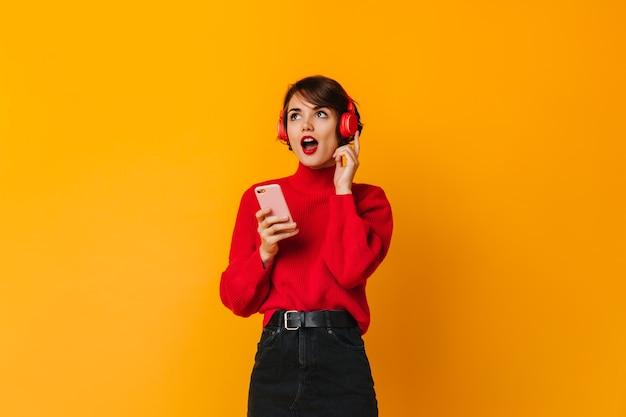 Erstaunte frau, die mit kopfhörern und smartphone aufwirft