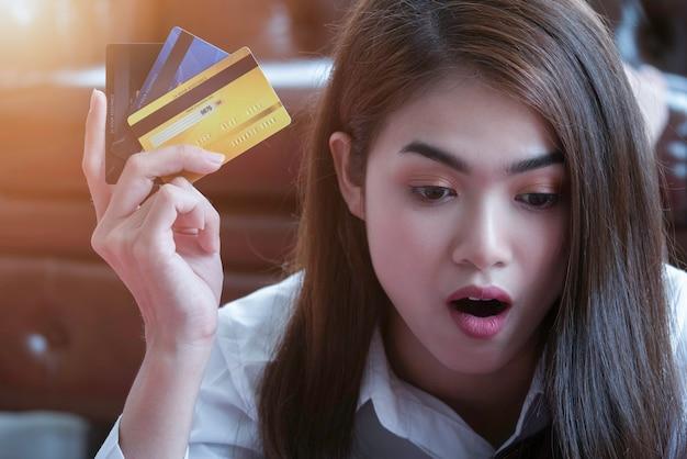 Erstaunte frau, die online zu hause mit kreditkarte im wohnzimmer kauft