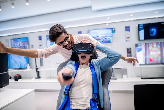 Erstaunte frau, die vr-brille ausprobiert und auf dem interaktiven vr-sitz sitzt. in der hand halten fernbedienung.