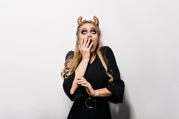 Erstaunte frau im eleganten kleid, das in halloween aufwirft. gut aussehende hexe, die überraschte gefühle ausdrückt.